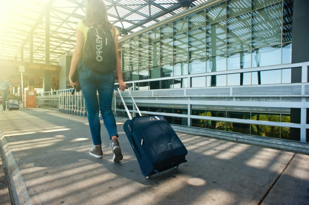 woman walking into airport with suitcase