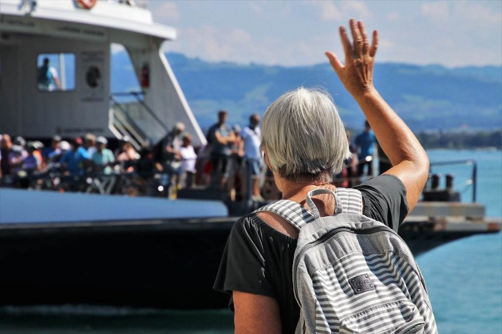 older lady waving at people on boat